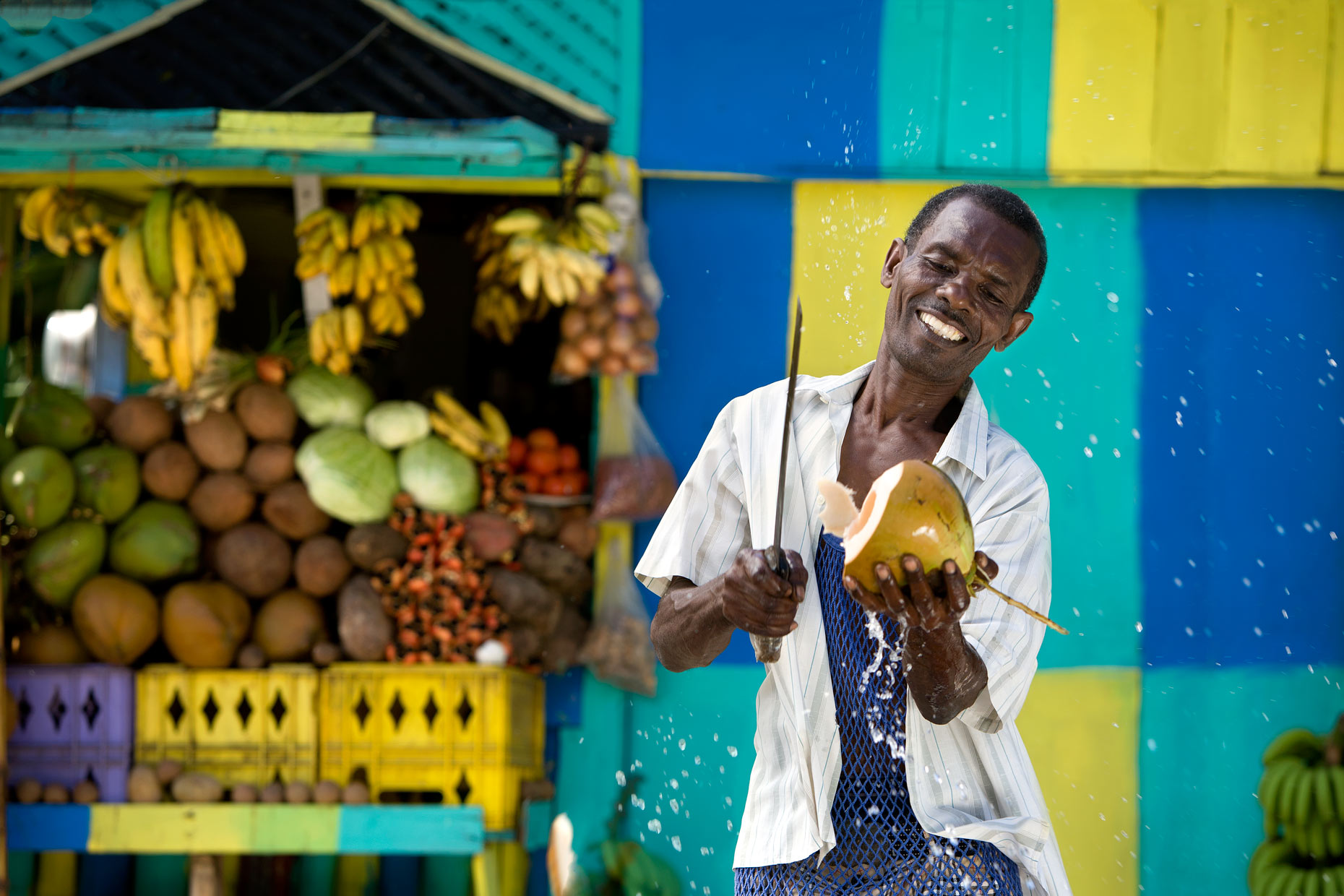 man cutting coconut on street in Jamaica