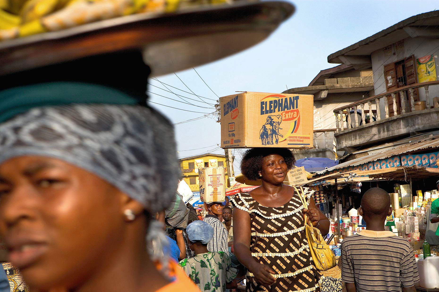 Woman carrying box on head through market