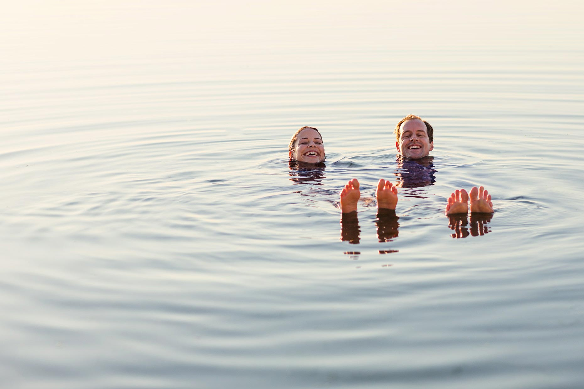 Couple smiling and floating in water