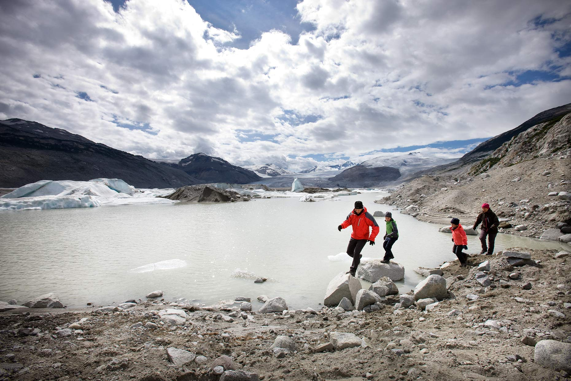 family-running-around-edge-of-glacier