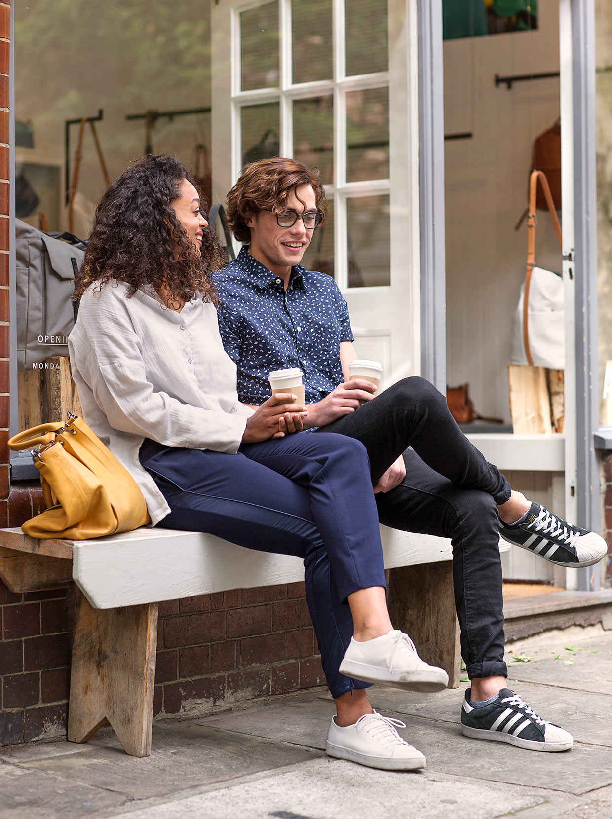 Fashionable couple sit outside shop with coffee