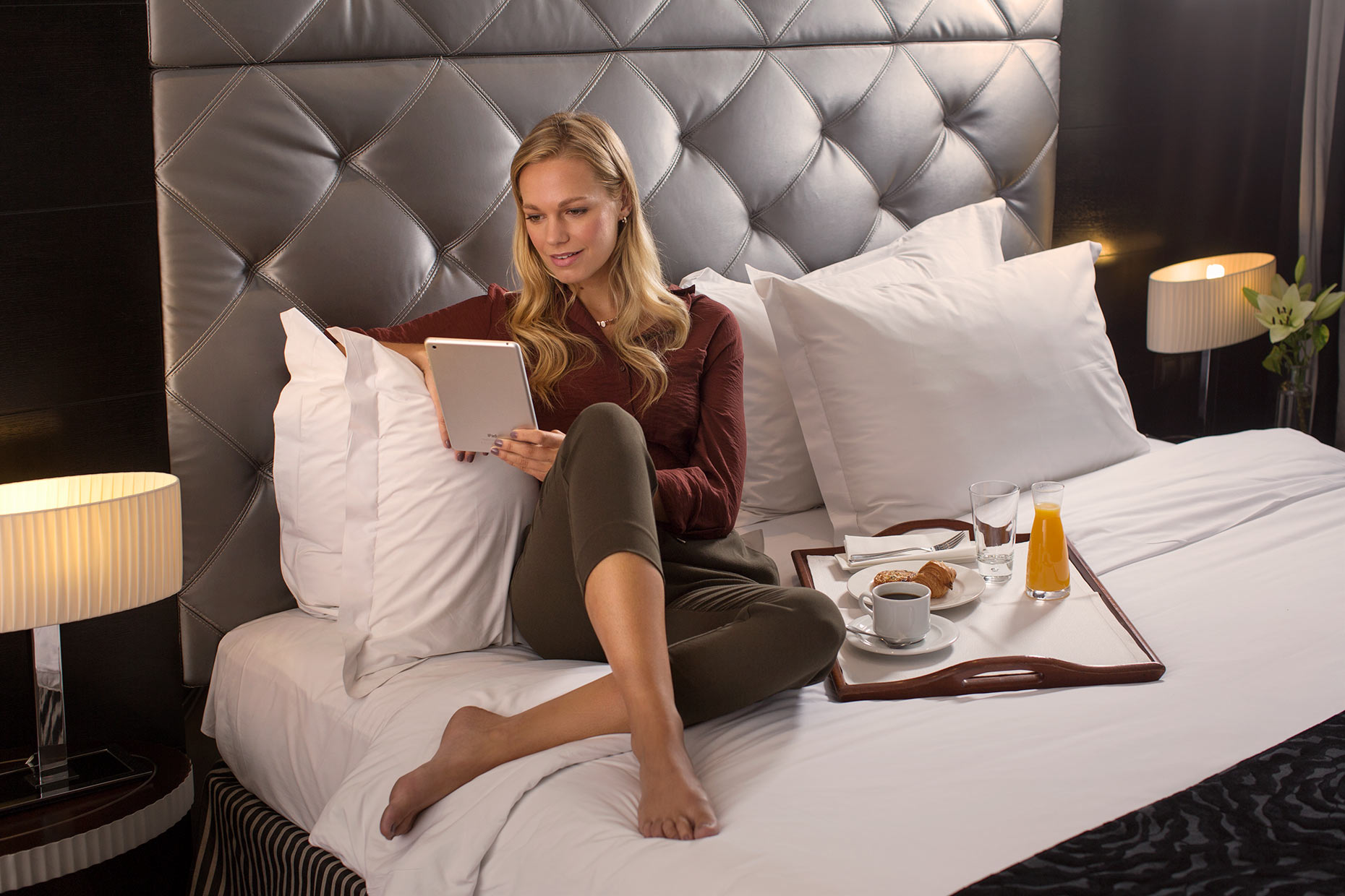 woman sitting on bed in hotel with tablet