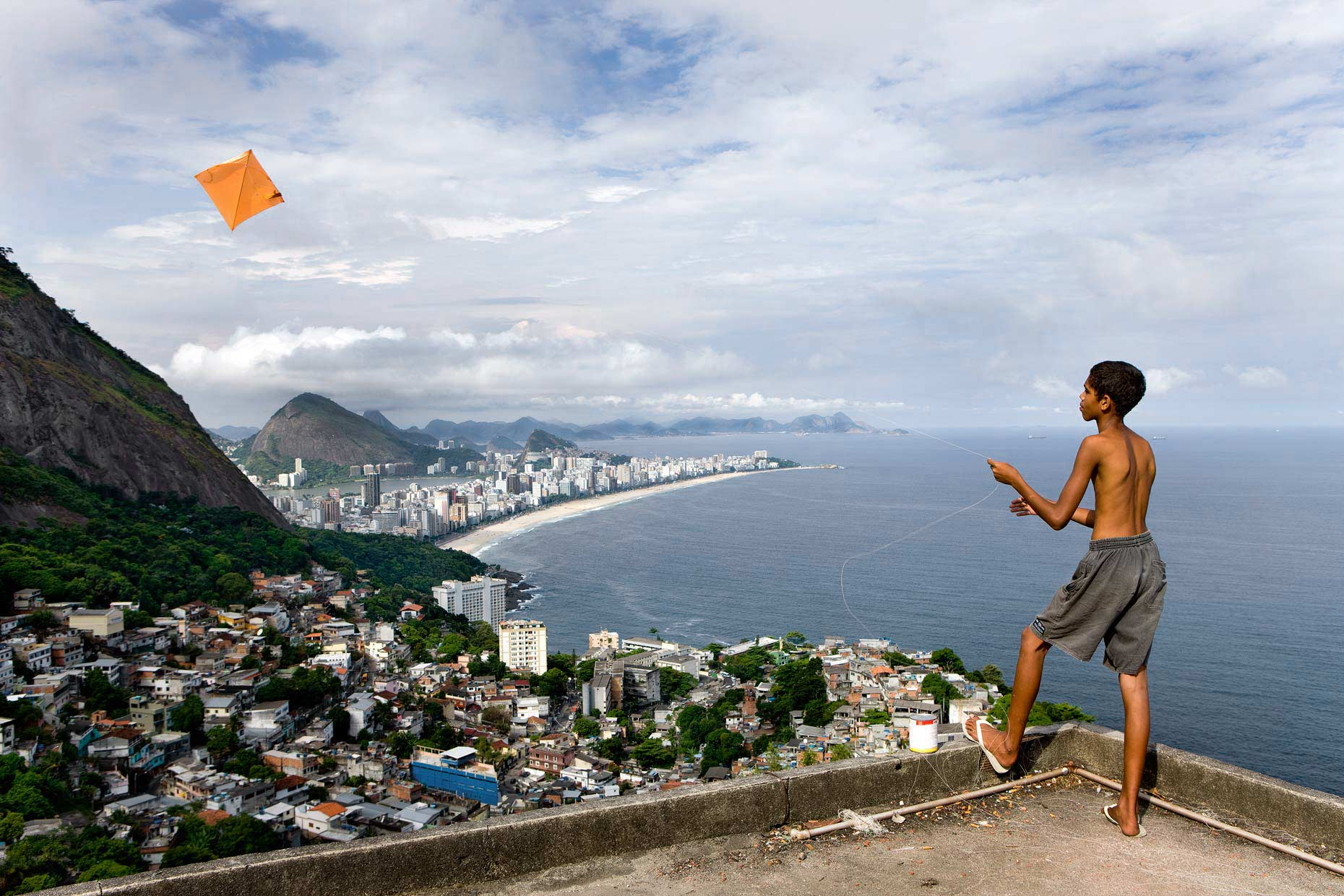 Boy playing with kite with view of Rio de jainero behind him